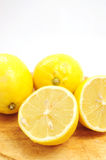 Lemons on wooden board. Whole and half lemons on wooden board Stock Photos