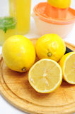 Lemons on wooden board. Lemons as ingredients to lemonade, bottles and sqeezer in the background Royalty Free Stock Photo