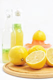 Lemons on wooden board. Lemons as ingredients to lemonade, bottles and sqeezer at the background Stock Images