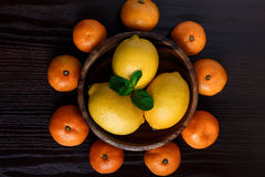 Lemons in wooden plate with mandarines and mint leafs on dark background close-up macro Stock Photos