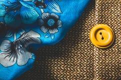 Lenço azul com teste padrão de flor e botão amarelo no fundo marrom de matéria têxtil Imagens de Stock Royalty Free