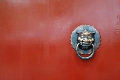 León chino en puerta roja Imagen de archivo