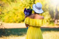 Lena_Misha-Dasha Femme arrière dans la robe jaune, chapeau, fleurs ! Image stock