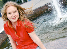 Lena smiles. The blond girl with green eyes in the red blouse is smiling against the fountain Royalty Free Stock Photography