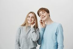 Lend me your ears. Friendly satisfied good-looking boyfriend and girlfriend, sharing earphones while listening favorite. Song, discussing music tastes during royalty free stock photos
