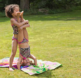 Lending a helping hand. Big sister helping little sister stand on her head Stock Photo