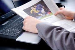 Lendo a notícia dos esportes Fotografia de Stock