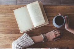 Lendo um livro e bebendo o café no café Fotografia de Stock Royalty Free