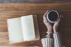 Lendo um livro e bebendo o café no café Fotos de Stock Royalty Free