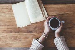 Lendo um livro e bebendo o café no café Fotografia de Stock