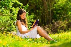 Lendo um sol do livro na primavera foto de stock