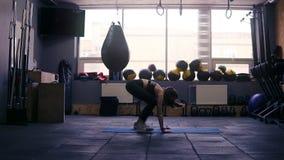 Lengte die van een sportief donkerbruin meisje die bij de gymnastiek uitwerken, in plank op vloermat springen Geschiktheid en gez stock footage
