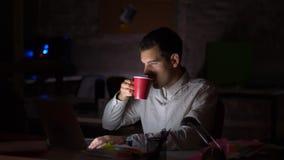 Lengte die van knappe Kaukasische mannelijke zitting bij Desktop, aan zijn laptop, licht werken die voor het scherm glanzen terwi stock videobeelden