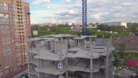 Lengte een bouwwerf met een blauwe kraan in de bouw met meerdere verdiepingen van grijs monolithisch beton waarop het werkmensen  stock footage