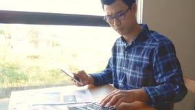 Lengte, ernstige Aziatische bedrijfsmens met administratie werken en calculator die voor berekeningendocumenten bedrijfsboekhoudi stock videobeelden