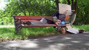 Lengte met oude gedronken landloper, die op bank in de straat slapen stock video