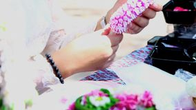 Lengte Thaise vrouw die tot een traditie maakt Thaise bloemenslinger stock videobeelden