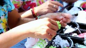 Lengte Thaise vrouw die tot een traditie maakt Thaise bloemenslinger stock video