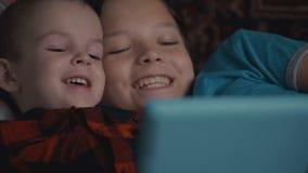Lengte twee jongens die tabletpc met behulp van die op bank liggen stock video