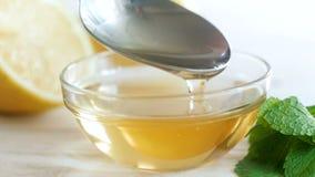 Lengte van de close-up de langzame motie van honing die van metaallepel druipen in kruik stock videobeelden
