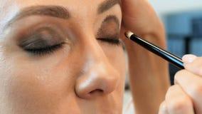 Lengte van de close-up de langzame motie van professionele visagiste het schilderen modellenogen Maeupkunstenaar die make-up op m stock video