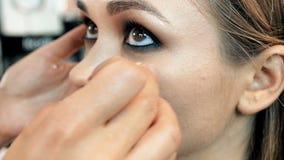 Lengte van de close-up de langzame motie van professionele visagiste het schilderen modellenogen Maeupkunstenaar die make-up op m stock videobeelden