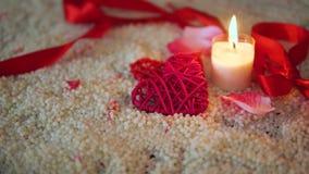 Lengte van de dag van decoratievalentine, lint en kaars het branden op zand stock videobeelden