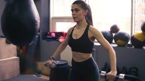 Lengte van een atletisch vrouwelijk brunette die met domoren uitwerken Gezonde levensstijl, geschiktheid, welzijn stock footage
