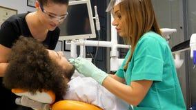Lengte van een vrouwelijke tandarts en haar medewerker die de tanden van een jonge mancontroleren stock videobeelden