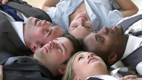 Lengte van het Commerciële team ontspannen op vloer in bureau stock footage