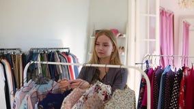 Lengte van het rek van de kledingskleding met hangers en uitrustingen in de winkel Het jonge mooie meisje probeert aan koos modie stock video
