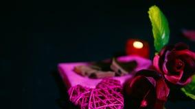 Lengte van het roze, kaars branden, chocolade en decoratie Valentine stock footage
