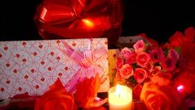 Lengte van impuls, giftdozen, bloem en kaars het branden Valentine-decoratie stock footage