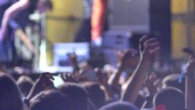 Lengte van menigte bij rotsoverleg bij nacht, mensen die handen opheffen stock footage