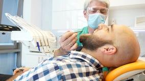 Lengte van tandarts controleren patiëntentanden stock video