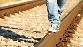 Lengtedraaien kleurrijk van zwart-wit: een persoon loopt langs spoorweg die tennisschoenen dragen stock video
