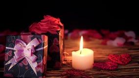 Lengteonduidelijk beeld van giftdozen, bloemblaadjes en kaars het branden De dag van de valentijnskaart stock footage