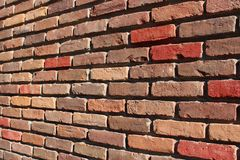 Length of red and brown brick wall showcases craftsmanship of mason who constructed it. Beautiful old red and brown brick wall of building`s exterior showcases stock photos