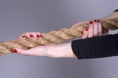 Length of rope and woman`s hands. Woman`s hands with painted nails gripping a rope Royalty Free Stock Photo