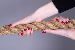 Length of rope and woman`s hands. Woman`s hands with painted nails gripping a rope Stock Photo