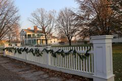 Length of white picket fence decorated for holidays, Genesee Country Village and Museum, New York, 2017. Long white picket fence and stately homes decorated for stock photography