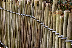Length of wood posts tied together with heavy rope Stock Image