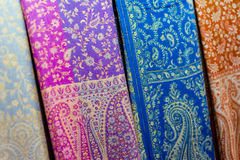 Lengths of colored fabric. Colorful textured background composed of lengths of blue, purple, brown and beige patterned cloth side by side on market stall in Royalty Free Stock Image