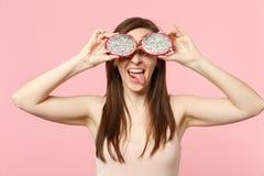 Lengua divertida de la demostración de la chica joven que cubre ojos con los halfs de la fruta madura fresca del dragón del pitah imagen de archivo