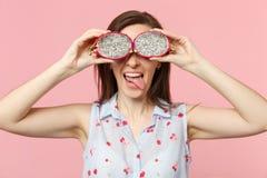 Lengua divertida de la demostraci?n de la chica joven que cubre ojos con los halfs de la fruta madura fresca del drag?n del pitah imagen de archivo libre de regalías