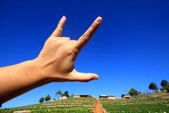 Lenguaje de signos en el cielo azul Imagenes de archivo