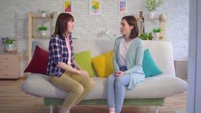 Lenguaje de signos sordo hermoso de dos aplicaciones de mujeres jovenes en la sala de estar almacen de metraje de vídeo
