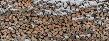 A lenha é armazenada na neve como uma textura de madeira imagens de stock royalty free