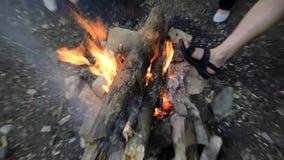 Lenha de queimadura no fogo e para aquecer os pés em torno do fogo vídeos de arquivo
