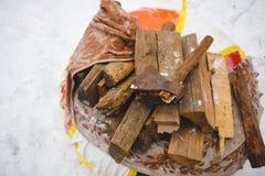 Lenha e machado na neve Desbastando a madeira Foto de Stock Royalty Free